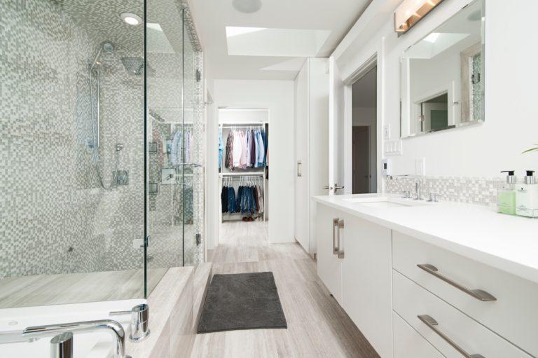 Es ist ein weiß gehaltenes Badezimmer zu sehen, durch welches man direkt in einen Kleiderschrank mit Hemden und Hosen schauen kann. Links vor der großen, mit weiß-grauen Mosaiksteinen verzierten Dusche liegt ein grauer Badteppich. Es wirkt alles sehr hell und offen.