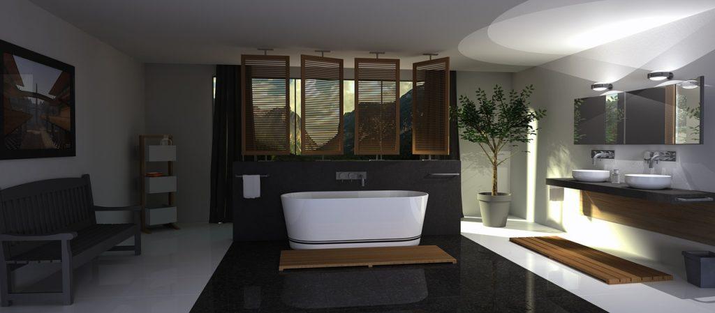 Man blickt in ein dunkles Badezimmer. in der Mitte steht eine weiße freistehende Badewanne und davor liegt ein Badteppich aus Holz. Dahinter ist ein Sichtschutz nach außen aus Holz. Es gibt auf der rechten Seite zwei Waschbecken, einen großen Spiegel und auch einen aus Holz bestehenden Badteppich. Links neben den Waschbecken steht ein kleines Bäumchen. Auf der linken Seite des Badezimmers steht eine Sitzbank worüber ein Bild aufgehangen wurde. Rechts neben der Bank steht ein kleines Regal.